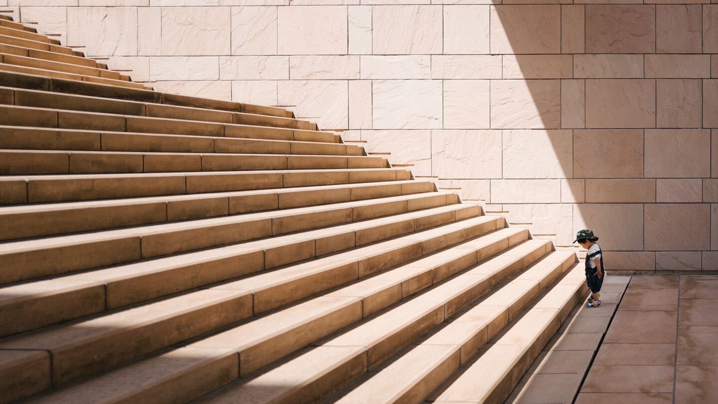 toddler standing in front of beige concrete stair
